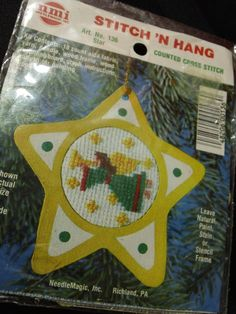 Needlemagic Inc., Stitch N Hang Counted Cross Stitch Kit Art No. 136 Star. Kit Contains: 18 count aida fabric, yarn, needle, wood frame, wood mounting board, graph, instructions, pattern for painting wood frame. Create a great keepsake for your tree this year!  Vintage kit is still sealed in original packaging. There is some wear on the outer package, but all contents are like new.