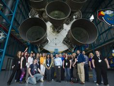 NASA Deputy Administrator Lori Garver, in yellow jacket, stands with participants from the NASA Social underneath the engines of the Saturn V rocket at the Apollo Saturn V visitor center, Thursday, May 18, 2012, at Kennedy Space Center in Cape Canaveral, Fla.