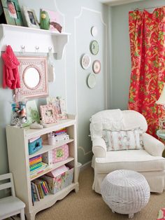 Soft teal walls create a great contrast against the curtains made from bright coral fabric for a color palette that's not typical for a little girl's room. Decorative plates match the mirror's cutout above the bookshelf. A white armchair and white wicker ottoman provide a comfortable place to read.