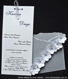 Tema Prata com Flores Brancas    Ficha Técnica:    Materiais utilizados: papel Marrakech na cor Trigo 180g/m² (interno), papel Relux na cor Aluminium 180g/m², papel Relux na cor Pérola Branca 180g/m² (externo);    Formato: 9,5cm (Largura) X 18cm (Altura);    Acabamento do convite: flores confeccionadas através da técnica de furadores com efeitos tridimensionais (3D), fitas prateadas e ilhoses;