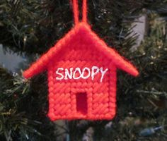 This handmade doghouse ornament celebrates the coolest dog in the universe - Snoopy from the Peanuts. It's 3 inches long, 3 inches wide and 2.5 inches high, made out of plastic canvas and yarn.