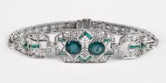 ART DECO PLATINUM, DIAMOND, AND EMERALD BRACELET. Comprised of two round emeralds, baguette emeralds, trillion emeralds, and round diamonds