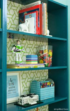 pair of Billy shelving units from Ikea,painted in Benjamin Moore's Galapagos Turquoise and backed in a green and white trellis pattern wallpaper . Green felt bins were added to help coral toy cars, smaller games and Legos of course! A tree floor lamp with movable lights serves as a bedside reading lamp. House of Turquoise: Guest Blogger: Cristin from Simplified Bee