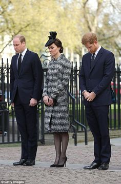 Prince William, Kate and Prince Harry stand silent during the service...