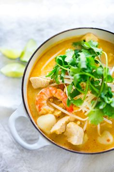 Laksa Soup with Malaysian style coconut curry broth, chicken or shrimp over rice noodles with fresh bean spouts, lime and cilantro.   #laksa #laksasoup #coconutnoodlesoup www.feastingathome.com