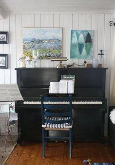 black piano, magazine rack next to piano.