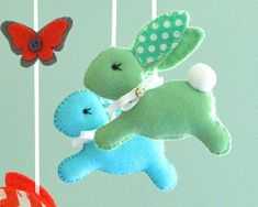 Baby Bunny Mobile This beautiful mobile is MADE TO ORDER This mobile consists of 4 cute bunnies handstitched using premium wool blend felt, in coral, mint green, lemon yellow,turquoise with a dot fabric on the ears. Hanging in the centre is a coral bunny with chevron ears. Around each