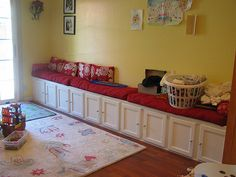 Unfinished cabinets from Lowes = bench seating & storage!  What a great idea for a playroom!