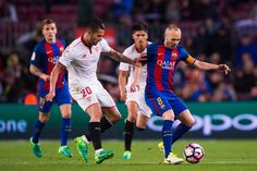 Andres Iniesta of FC Barcelona conducts the ball past Victor Machin 'Vitolo' of Sevilla FC during the La Liga match between FC Barcelona and Sevilla FC at Camp Nou stadium on April 5, 2017 in Barcelona, Catalonia.