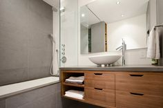 Duravit and Hansgrohe fixtures with European-sized grey bathroom tile.