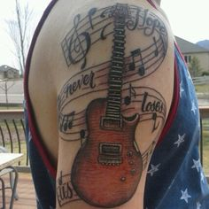 Love the musical notation in the background of the tattoo. Photo by britainbuxton1. Play guitar? Check out www.guitarjar.co.uk - Guitar Magazine.
