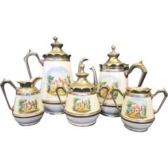 This is a antique six piece pewter and granite ware coffee and tea service with a castle scene.  Although this set is unmarked, it is undoubtedly