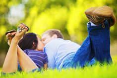 Cute couple pose kissing in grass.