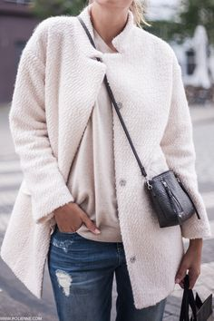 Paulien Riemis is wearing a white fluffy coat from C&A, knit top from Hush and jeans from Tally Weijl