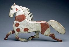 FOLK ART CARVED WOODEN HORSE IN RED AND WHITE PAINT, LATE NINETEENTH CENTURY.