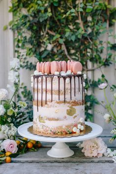 The Hottest Trend in Wedding Desserts: Drip Cakes | Blush funfetti masterpiece semi-naked cake with gold foil and topped with pink macarons by Scootabaker