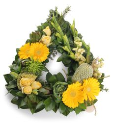 Yellow funeral, sympathy arrangement with gerbera daisies, kale, celosia, gladiolas, leucodendron.