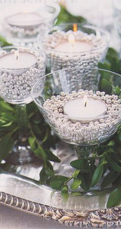 Wine/martini glasses filled with silver, gold or pearl beads and a tea light. so pretty & reflects the light.
