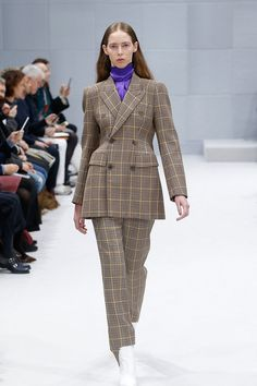 A model walks the runway at Balenciaga's fall-winter 2016 show wearing a plaid jacket and trousers