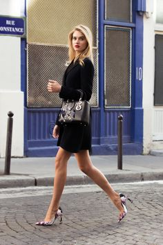 Street style fashion showing off her long legs in a little black dress and pointy toe stilettos