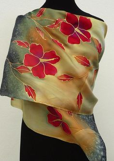 Red gold floral silk scarf with hibiscus flowers hand painted in fiery red , dark gold , gray , sage colors with black and red vines . The drawing of this wrap is made with metallic gold gutta which has a light feel on silk and makes the design precious. The last photo shows the silk still