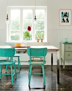 I love the big window, white walls, and especially the pop of bright color provided by the painted chairs.  Flowers in the windowsill are also a must!