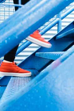 Person in Black Pants and Red High Top Sneakers Walking on Stairs