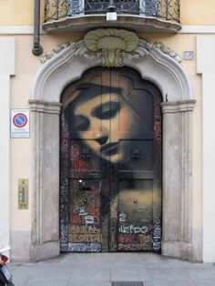 Talented graffiti artist El Mac adds a touch of beauty to gritty urban landscapes around the world with his stunning and almost dream-like photorealistic murals, like the one on this door in Milan