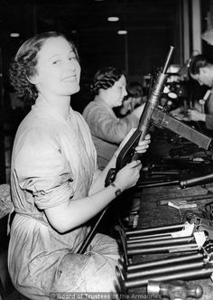 A British female defense worker completes the assembly of a Sten MkII submachine gun.