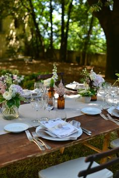 A rustic outdoor dining table with seasonable flowers and burlap runners. Time for dinners under the stars!