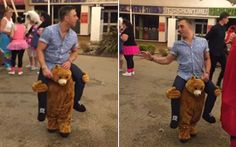Onlookers laugh as a man larks around in a pretty convincing piggyback ride costume