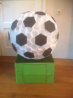 Surprise. Doos met kunstgras er op met een luikje voor het kadootje. Op het gras een enorme voetbal van plastic bekertjes. ( 225 stuks!)