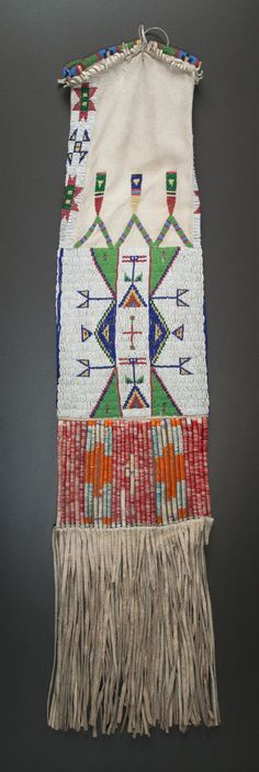 """AA SIOUX BEADED HIDE TOBACCO BAG, sinew sewn and lane-stitched in classic shades of glass seed beads, each side with a panel of geometric elements, surmounted by three """"feathers,"""" a panel of rawhide slats, wrapped with green, purple, orange and red-dyed porcupine quills, suspended below, thick hide fringe along the bottom. [Looks like a pipe bag to me. At 35""""? It's a pipe bag]"""
