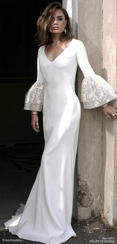 Fitted crepe gown. V-neckline and round open back. Long, puffy sleeves with embroidered tulle. Flowery elements, beads, sequins and silver thread.