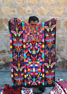 A man from Usila in northern Oaxaca displays a beautiful huipil from Valle Nacional (Chinantec) that he is hoping to sell during the holiday markets in the city of Oaxaca, Mexico