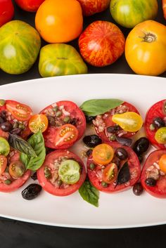 NYT Cooking: In the height of summer, a stellar but simple tomato salad is essential dinner party fare. This one has the distinct profile of a niçoise: Thick slices are arranged on a platter, then topped with a garlicky chopped olive vinaigrette and colorful halved cherry tomatoes. A flourish of anchovy plays against the sweet ripeness, and scattered basil leaves are both decorative an...