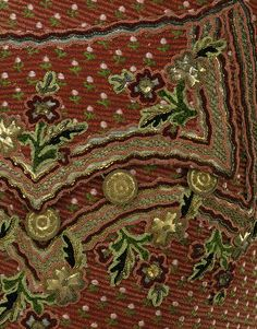 Detail: Waistcoat, France, 1760-69. Silk & linen, silver, gold, brass. Large petals of gilt-brass foil scatter across this opulent waistcoat. The use of such flashy decoration is typical of men's dress between 1750 & 1780. Foils were made of thin sheets of metal, usually silver or brass, that were often gilt or colored with enamel. Simple floral or leaf shapes were stamped out & perforated at the edges so they could be sewn to the fabric.
