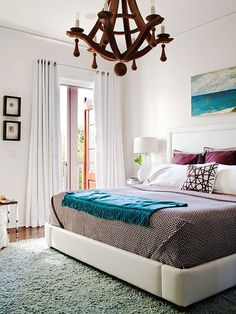 bedroom, plum and teal accents, very modern with upholstered baseboards for the bed