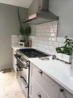 Grey Howdens burford kitchen with white subway tiles and white corian  worktop