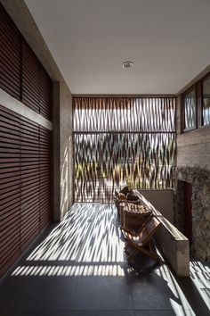 Modern Living Spaces // Entryway with grey concrete floors and wood walls paired with a  sculptural metal wall providing a layer of pattern and texture through the shadows and natural light, designed by Chauriye Stager Architects