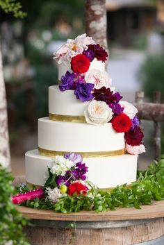 white wedding cake with red purple weddng flowers via Allison Maginn Photography - Deer Pearl Flowers / http://www.deerpearlflowers.com/wedding-cakes-desserts/white-wedding-cake-with-red-purple-weddng-flowers-via-allison-maginn-photography/