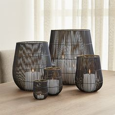 Delicate wire cage shelters candles in two-toned iron. Black exterior accentuates the delicate silhouette, while gold interior enhances candlelight's glow.