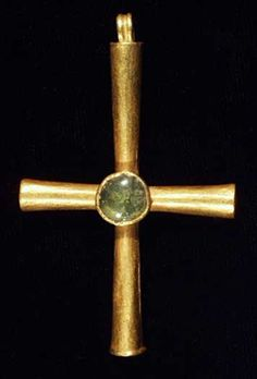 BYZANTINE GOLD AND GLASS CROSS EARLY VII c. A.D. Hollow conical arms and ribbed suspension loop. At the intersection of the arms, there is a truncated cone with a circular collar set with pale green transparent glass cabochon. 61 mm.