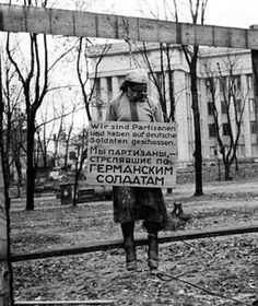 """Nurse at the Scherbatsevich hospital, Olga Fedorovna, hanged by the Germans in Alexander Square in Minsk, October 26,1941. The inscription on the poster hanging around her neck reads in Russian and German - """"We are partisans, shooting at German soldiers."""" Hanging was a favored tactic for small-scale killings because it has a more dramatic effect"""