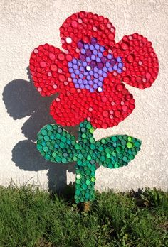 Les réalisations avec les enfants au cours des TAP. Des fleurs, supports en bois et bouchons en plastique recyclés.