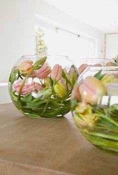 Tulpen in een bolvaas. Geef de tulp een nachtje geen water. De steel wordt dan slap waarna je hem in de gewenste vorm kan buigen. Snij de tulp weer schuin af en geef daarna weer water.De steel behoudt dan zijn gebogen vorm.