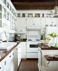 Stunning white kitchen design with off-white beadboard kitchen cabinets, glass-front cabinets, white subway tiles backsplash, butcher block countertops, white appliances and kitchen island. by belinda Butcher Block Kitchen, Butcher Block Countertops, Kitchen Countertops, Butcher Blocks, Dark Counters, Copper Countertops, Modern Countertops, Travertine Backsplash, Herringbone Backsplash