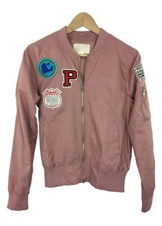 womens bomber jacket pink color Solid all throughout Features front patches and long sleeves with a zipper front closure Side pockets and finished hem 100% poly