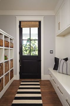 Black and white rug in front of door leads to the bathroom