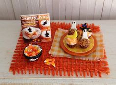 Miniature Halloween Cupcakes With Ghosts, A Moon, And A Witch On Top, A Bowl Of Candy Corn, And A Miniature Magazine